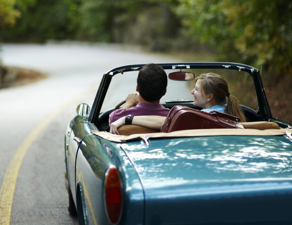Couple taking a road trip in a blue vintage convertible.